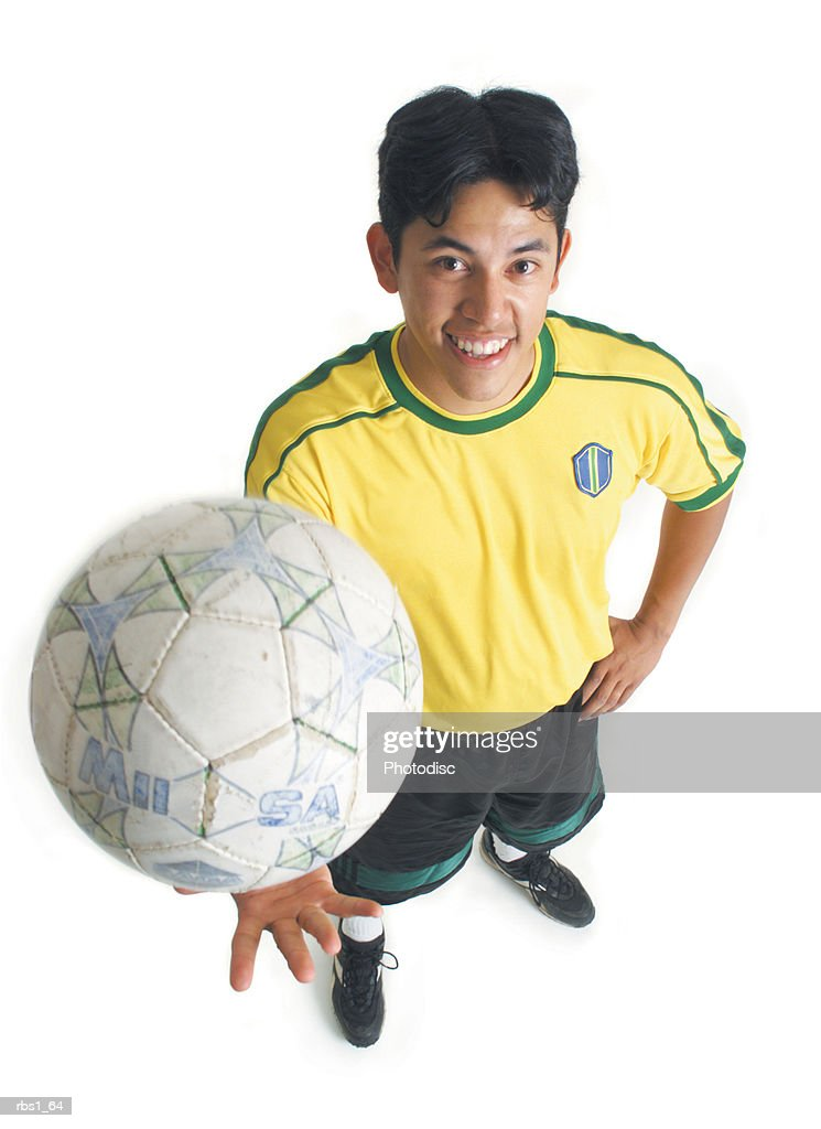 a young latin male in a yellow jersey tosses up a soccer ball and smiles as he looks up at the camera : Foto de stock