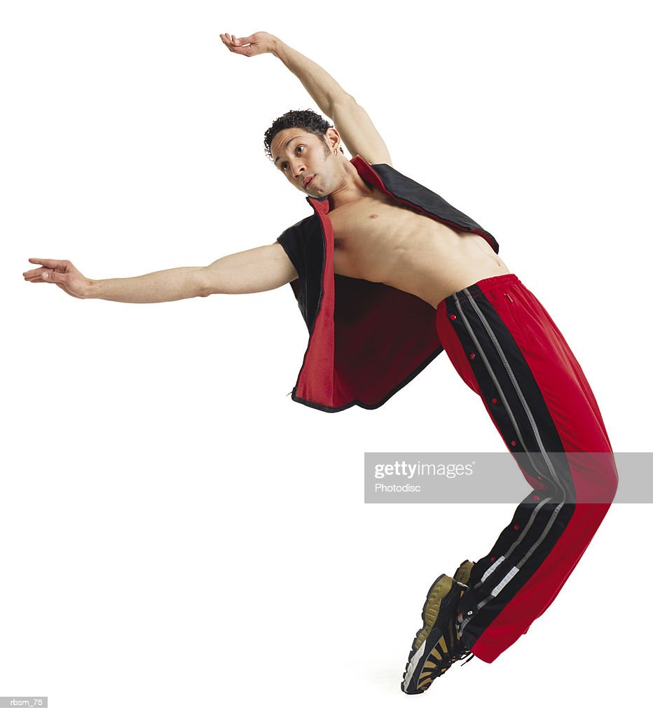 a young latin male modern dancer in red pants and a black vest and no shirt arches his back and balance on his tiptoes : Foto de stock