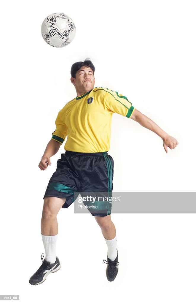 a young latin male wearing a yellow jersey jumps and hits a soccer ball with his head : Stockfoto