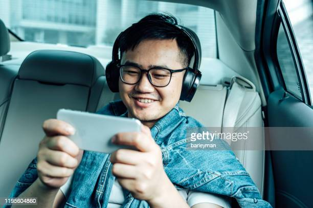 a young male play mobile game  in the car - leisure games ストックフォトと画像