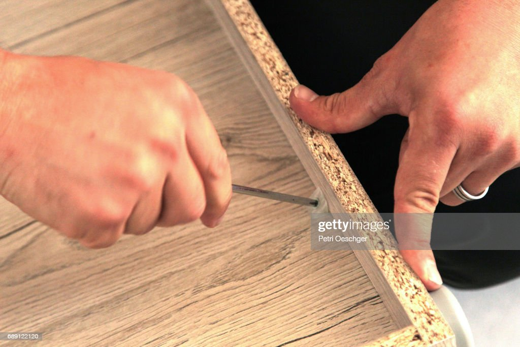 a Young man building a cabinet. : Stock Photo