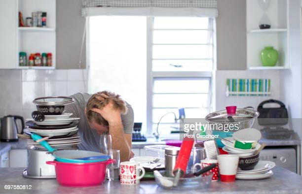 a Young man discouraged about washing a large amount of dishes.