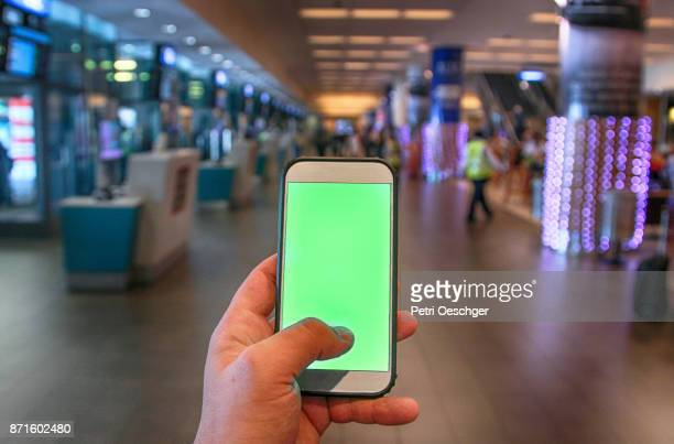 a young man holding a green screen smartphone at cape town international airport. - chroma key fotografías e imágenes de stock