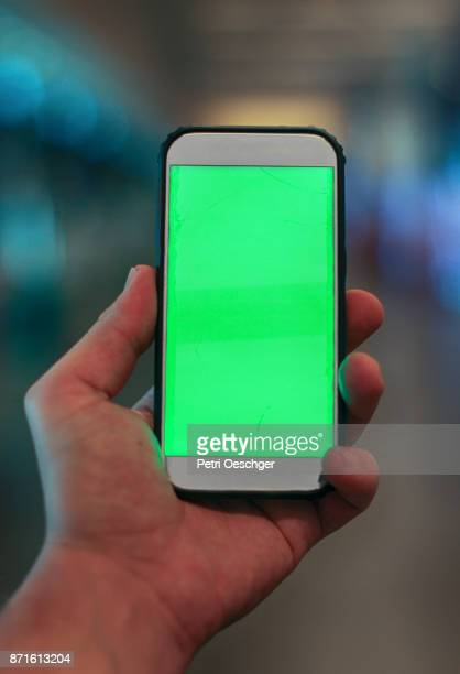 a young man holding a green screen smartphone at cape town international airport. - ホームページ ストックフォトと画像