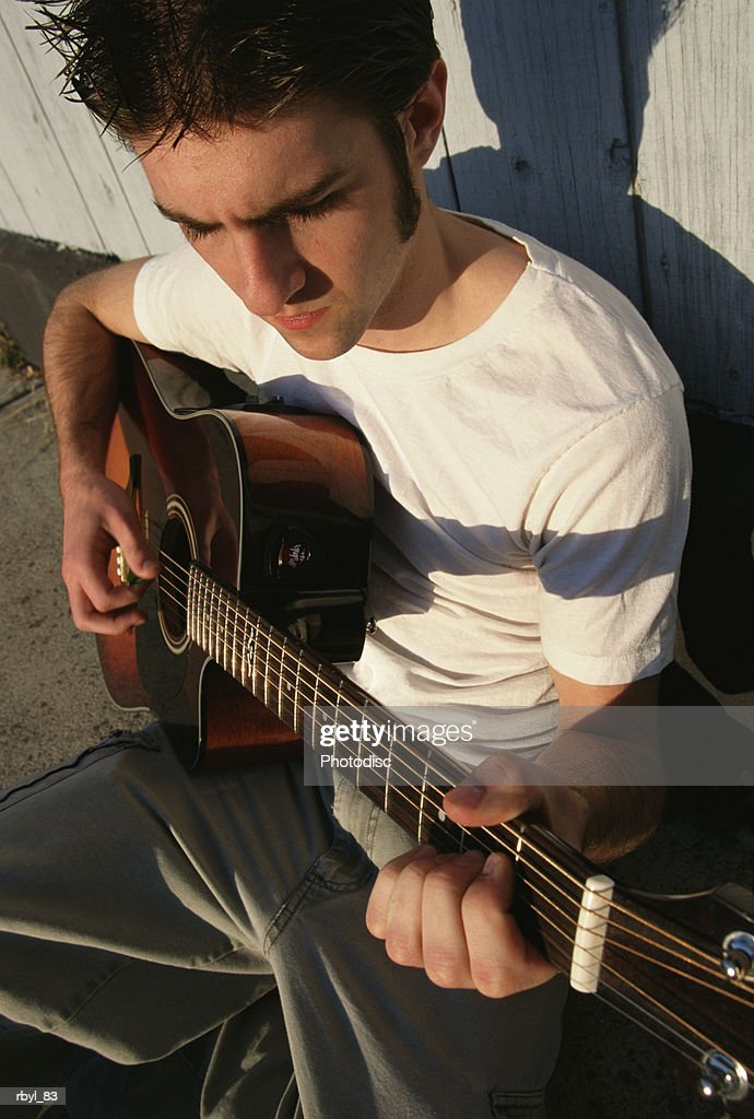 a young man in a white t-shirt and tan pants is sitting on a sidewalk playing his guitar : Foto de stock