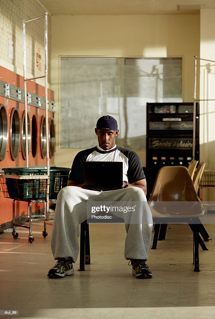a young man in grey sweatpants and a t-shirt is sitting in a laundromat typing on a laptop computer : Stockfoto