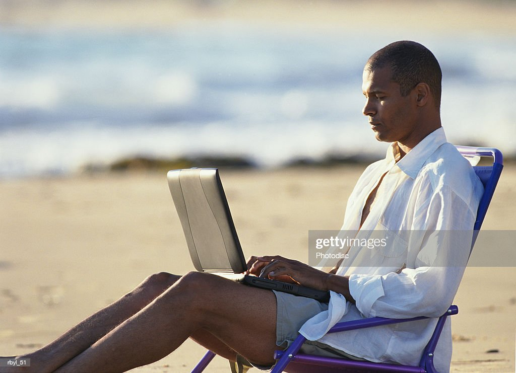 a young man in tan shorts and a white oxford shirt is reclining in a beach chair typing in to a laptop computer : Foto de stock