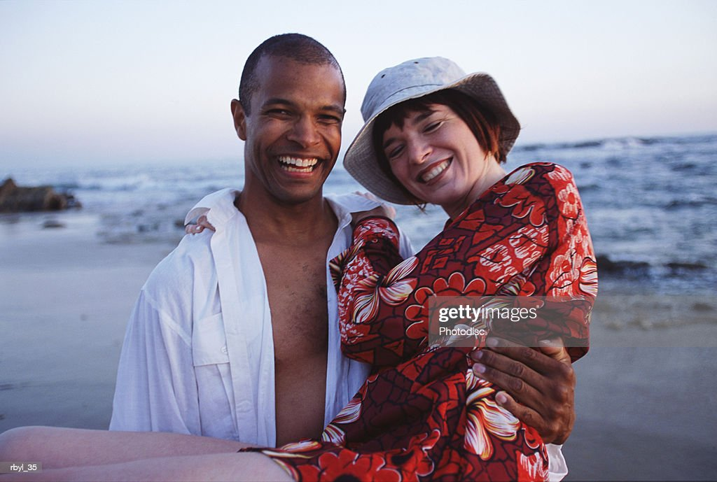 a young man is carrying a young woman in his arms with the beach and shoreline behind them : Foto de stock