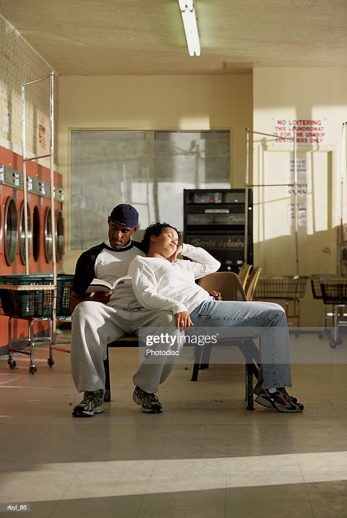 a young man is reading or studiying in a laundromat with his wife sleeping on his shoulder : Foto de stock