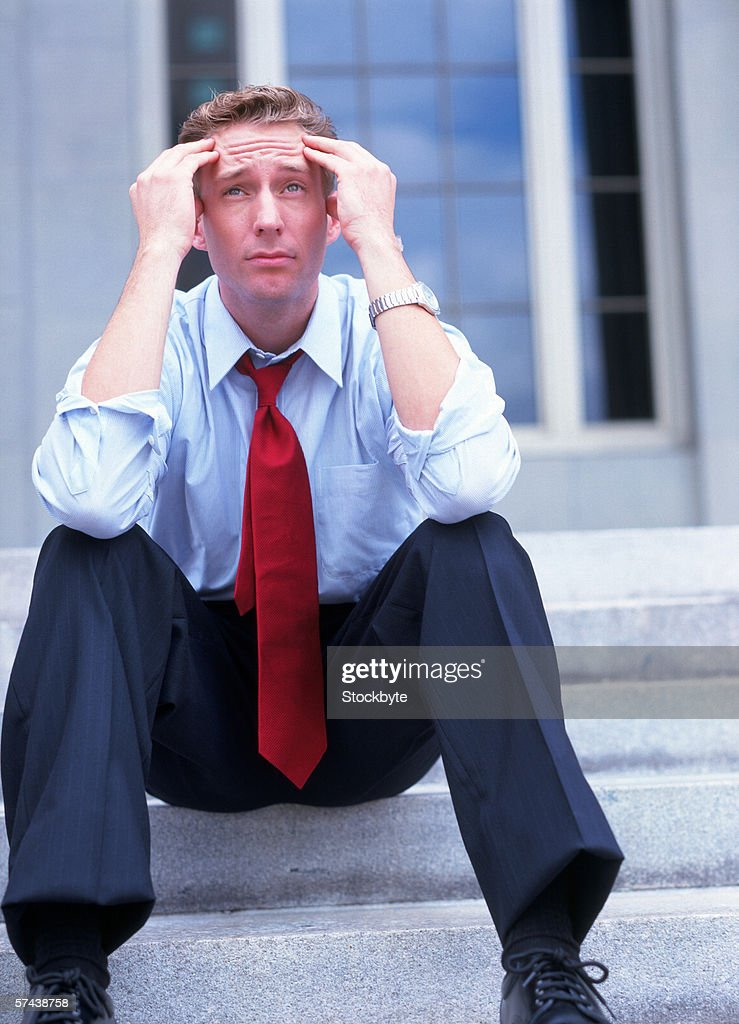 a young man sitting on the stairs holding his head : Stock Photo