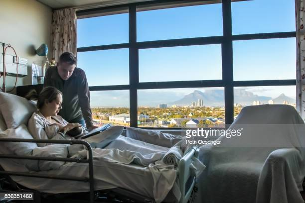a Young man spends time with his wife in hospital as she recovers from a caesarean section.