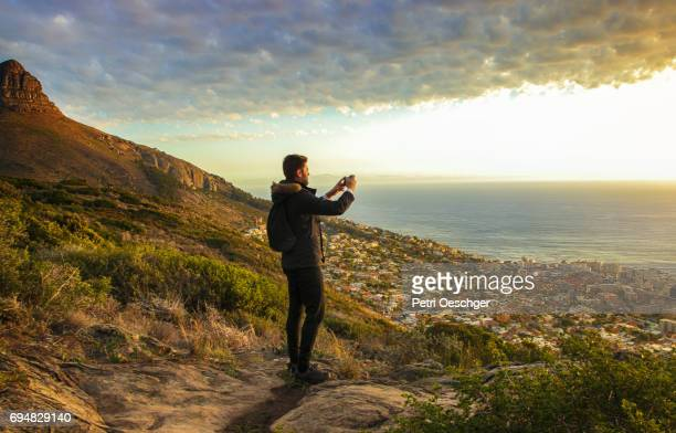 a Young man taking pictures of a beautiful sunset.