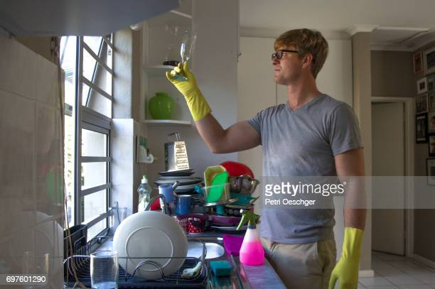 a Young man washing a large amount of dishes.