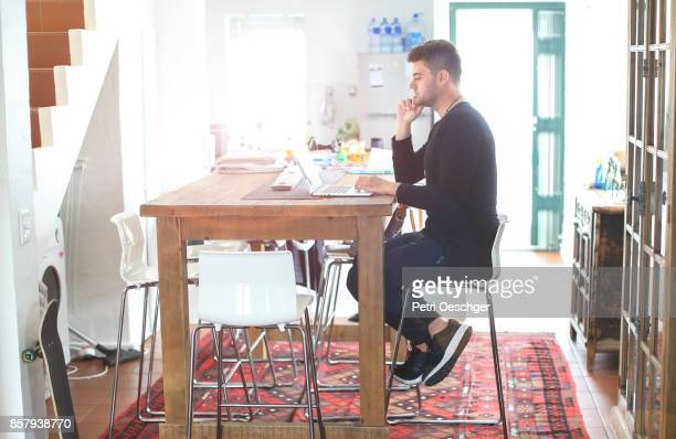 a young man working on his laptop from home. - bonne posture photos et images de collection