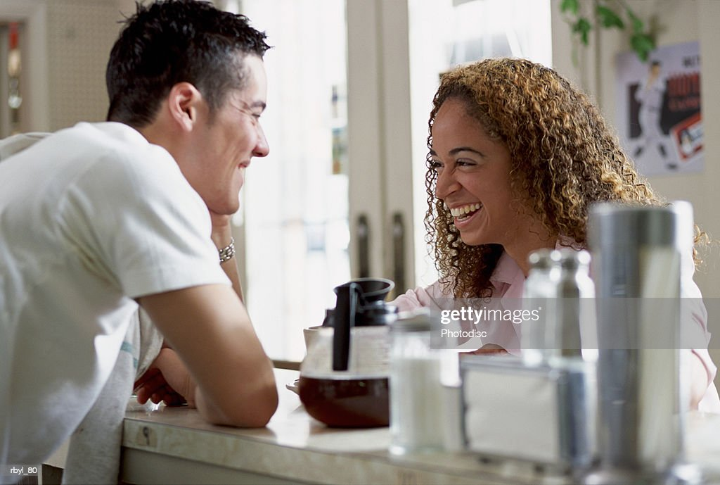 a young man working the counter of a restuarant or cafe is laughing and tlaking with a young woman with curly brown hair : Foto de stock