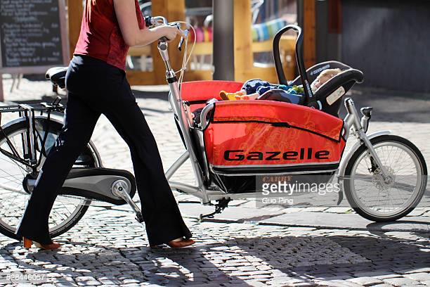 a young mom push the baby bicycle walking on the street