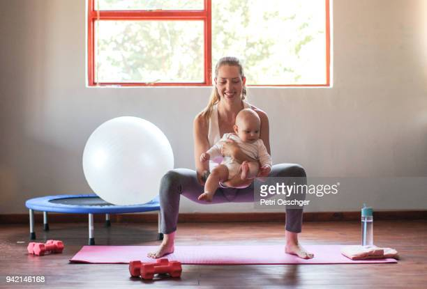 a Young mother exercising at home with her baby boy