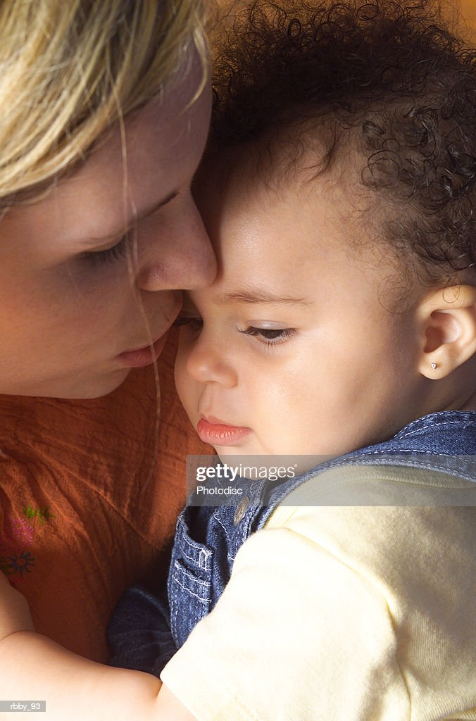 a young mother holds her african american daughter close to console her : Stockfoto