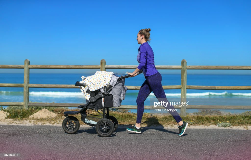 a Young mother jogging on the beachfront pushing a stroller. : Stockfoto