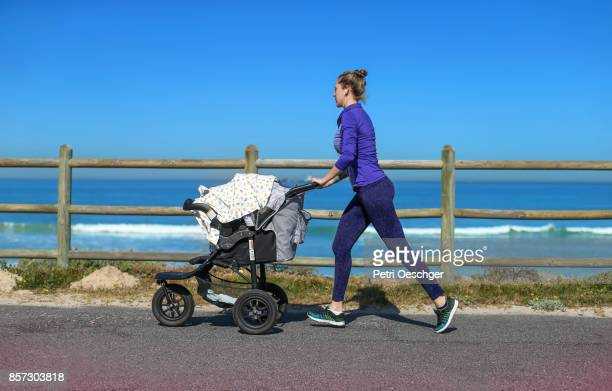 a Young mother jogging on the beachfront pushing a stroller.