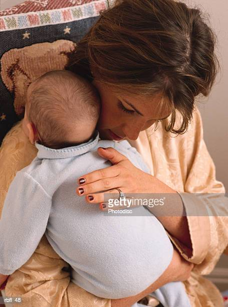 a young mothers burps and cuddles her newborn baby