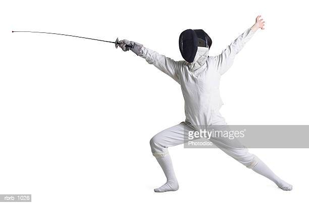 a young person in fencing gear holds out their sword as if fighting