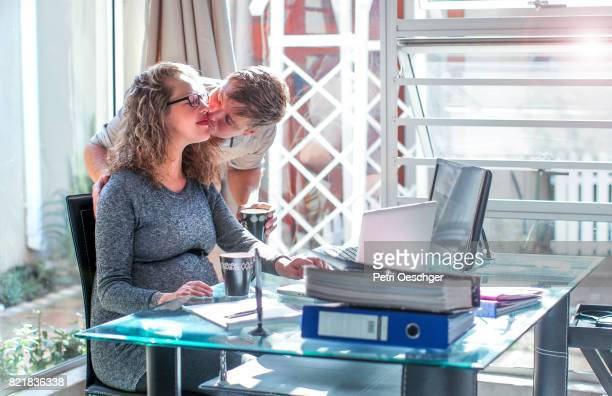 a young pregnant woman and her husband working together. - delegating stock photos and pictures