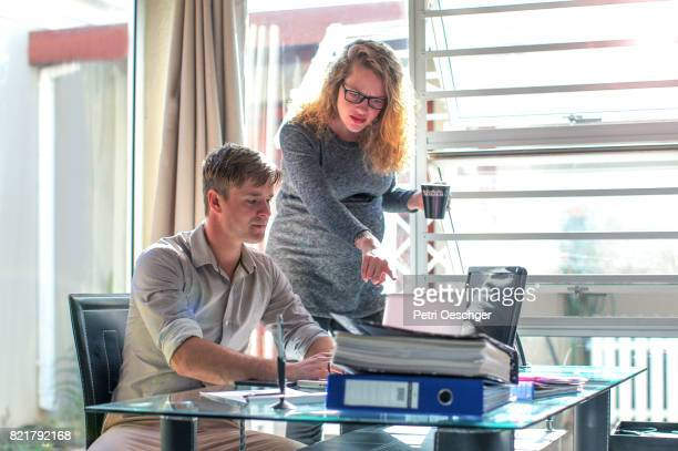 a young pregnant woman delegating to an employee. - delegating stock photos and pictures