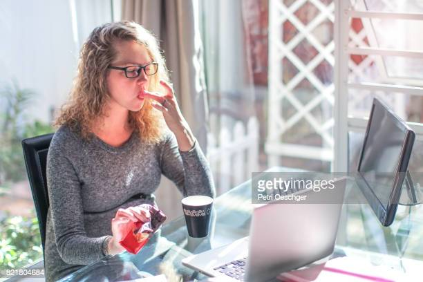 a Young pregnant woman eating chocolate at her desk at work.