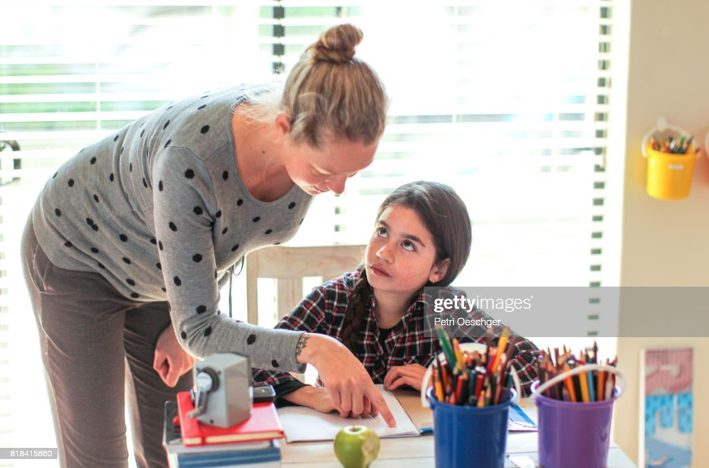 a Young pregnant woman helping a young girl with her homework on the computer. : Stock Photo
