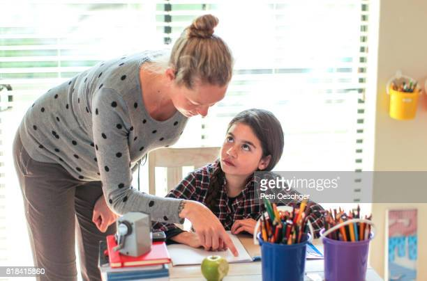 a Young pregnant woman helping a young girl with her homework on the computer.