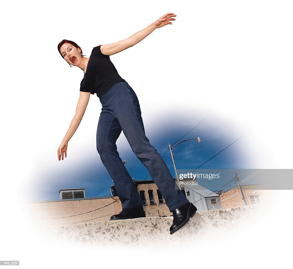 a young red haired caucasian woman in black boots wearing jeans and a black shirt is balancing along the top of a wall that is in front of some old buildings : Foto de stock