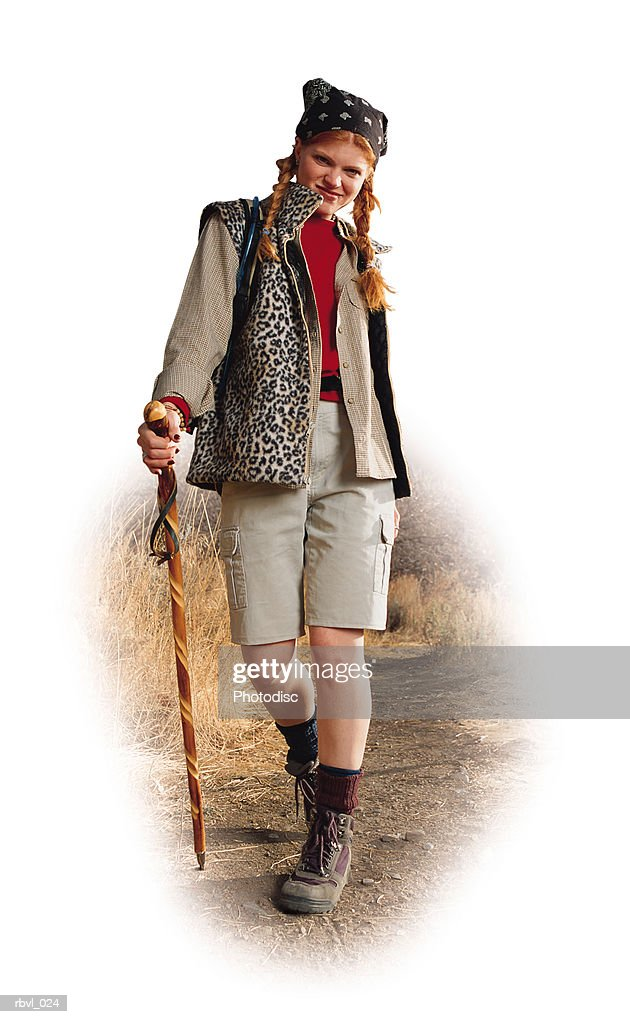 a young red headed caucasian woman in tan shorts and a tan long sleeve shirt is hiking down a trail with a walking stick in her hand : Stockfoto