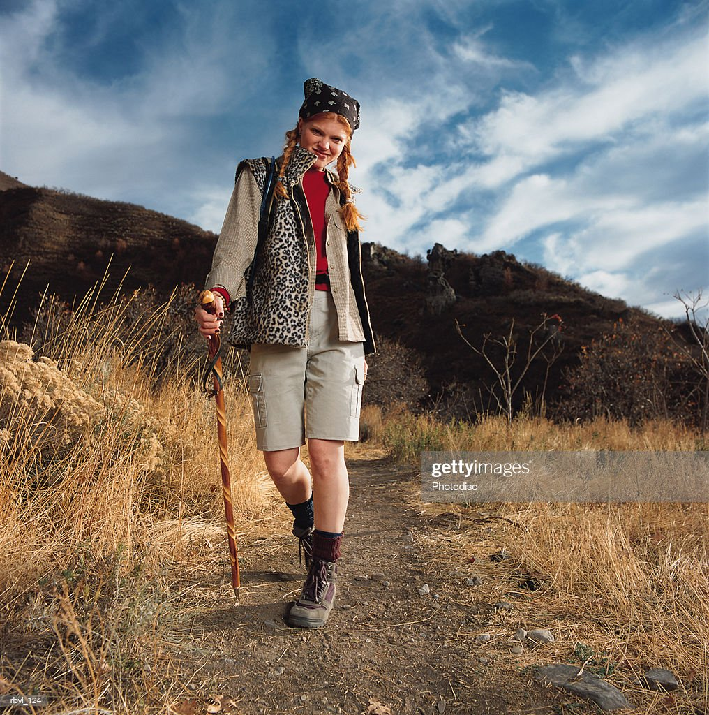 a young red headed caucasian woman in tan shorts and a tan long sleeve shirt is hiking down a trail with a walking stick in her hand : Foto de stock