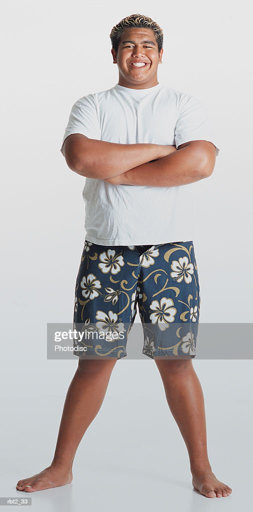 a young smiling hawaiian man with bleached hair wearing flowered shorts and a white teeshirt  stands barefooted with arms folded looking at the camera : Foto de stock