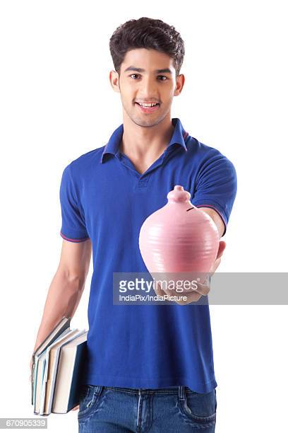 a young student holding books in one hand and money bank in the other