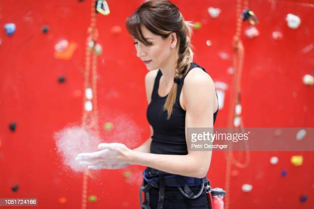 a Young woman applies chalk powder to her hands before climbing.