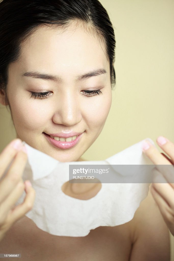 a young woman applying a treatment : Stock Photo