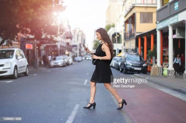 a young woman crossing the road. - passadeira via pública imagens e fotografias de stock