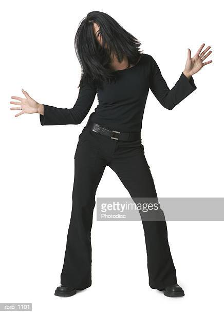 a young woman dressed in black strikes a fun pose and tosses her hair around