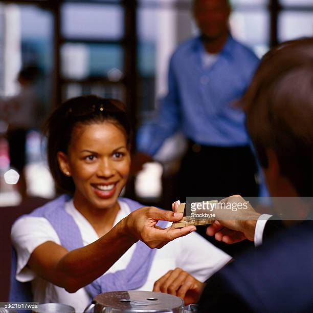 a young woman handing her credit card to a man across the table