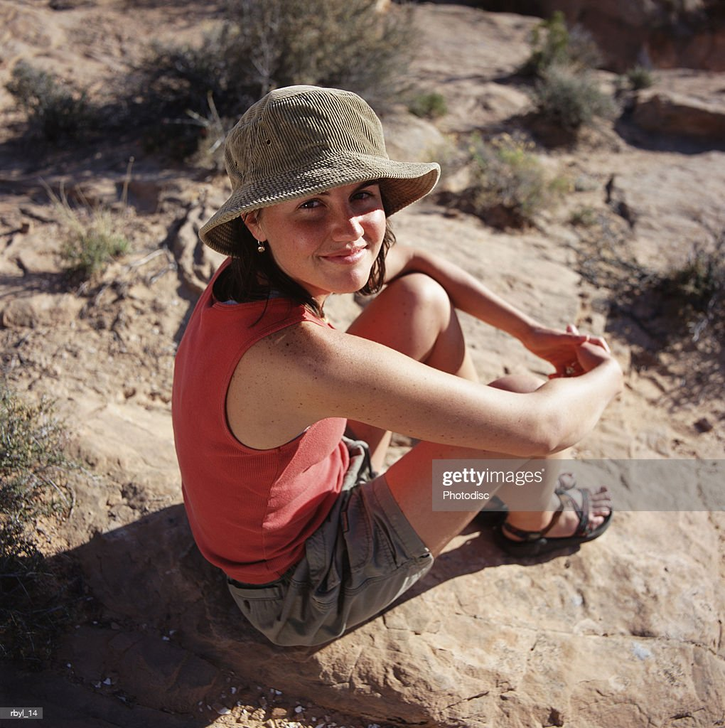 a young woman i n grey shorts a red shirt and tan hat is sitting on a rock in the south utah desert : Foto de stock
