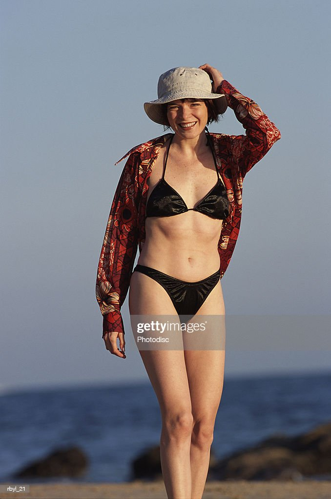 a young woman in a black bikini flowered shirt and tan hat is standing on a rocky beach with the ocean in the background : Foto de stock