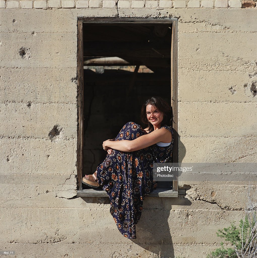 a young woman in a blue flowered dress sits in the window frame of an old abandoned building : Foto de stock