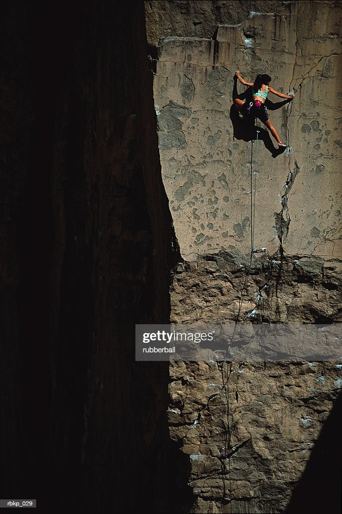a young woman in a blue sports bra and black shorts is climbing the face of a vertical rock that is partially hidden in shadow : Stockfoto
