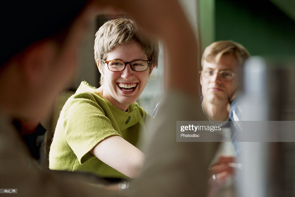 a young woman in a green dress and glasses is sitting at the counter of a diner or cafe and laughing and talking to her friends : Foto de stock