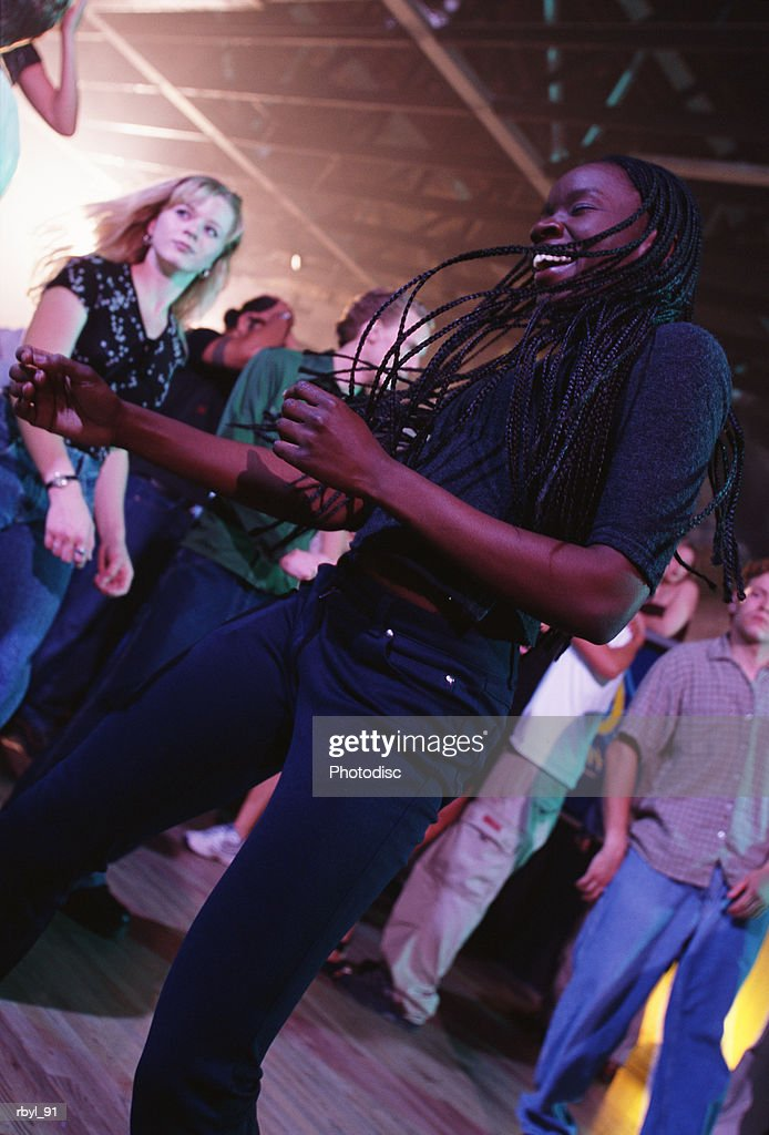 a young woman in a grey shirt and dark blue pants with long dark corn rows is dancing in a nightclub : Foto de stock