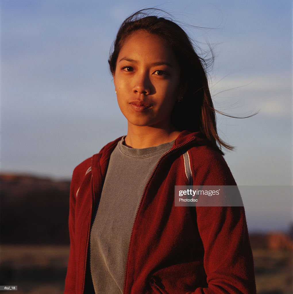 a young woman in a grey shirt and red jacket is standing in the south utah desert with the desert blurred in the background : Foto de stock