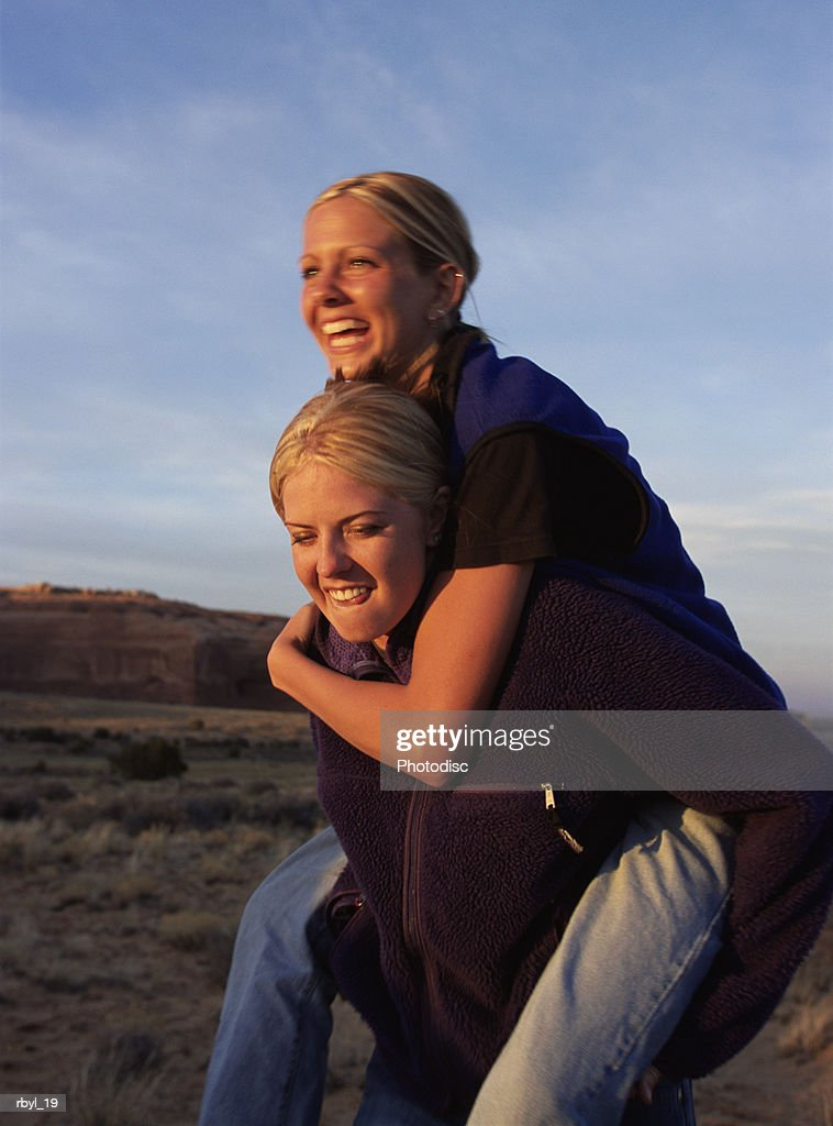 a young woman in blue jeans and a purple fleece is giving her friend who is wearing blue jeand and a blue fleece vest a piggyback ride with the southern utah desert in the background : Foto de stock