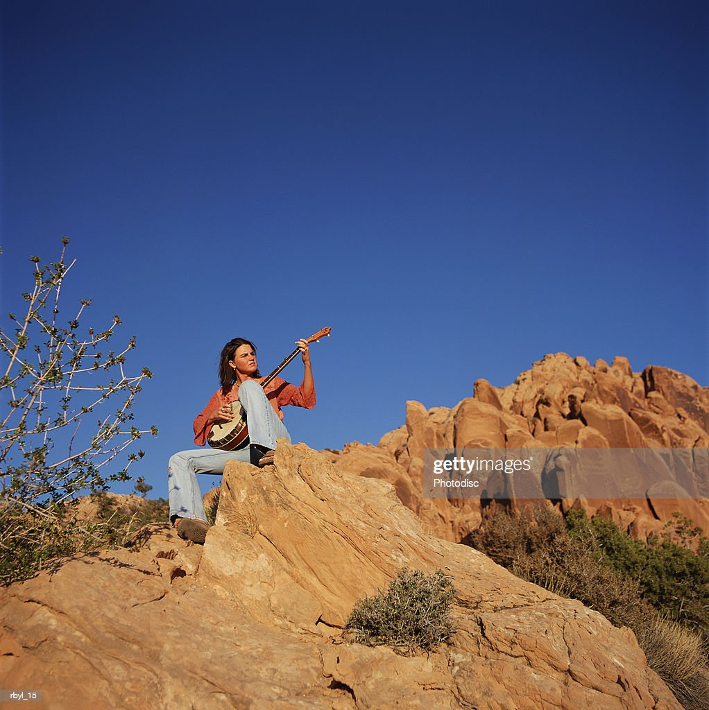 a young woman in blue jeans and a red long sleeved shirt is sittingn on the crest of a boulder playing a banjo with the blue sky and other rock croppings in the background : Foto de stock